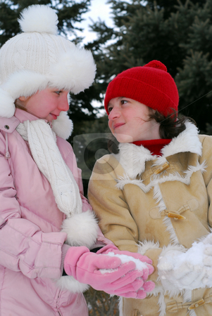 Two girls stock photo, Portrait of two young girls in winter park holding snowballs by Elena Elisseeva