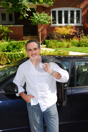 Man house car stock photo, A man standing outside leaning on his car in front of his house by Elena Elisseeva