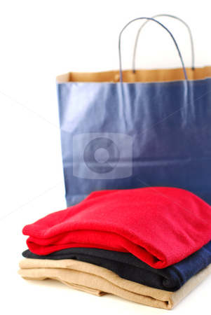 Clothes and shopping bag stock photo, Folded sweaters with a paper shopping bag on white background by Elena Elisseeva