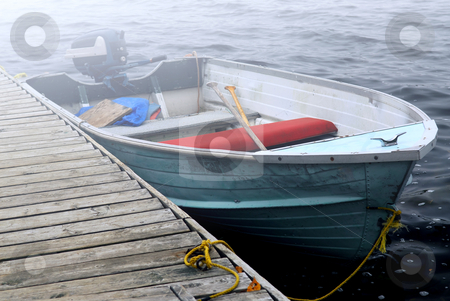 Boat in a fog stock photo, Empty old boat at a dock on a misty lake by Elena Elisseeva