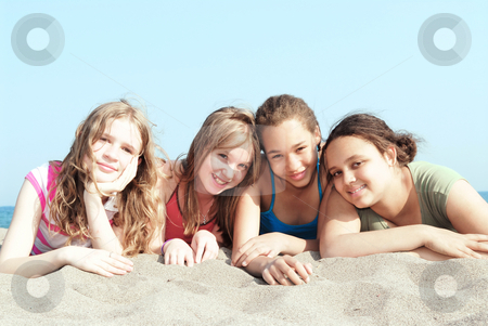 Four girls on a beach stock photo, Portrait of four young girls on a sandy beach by Elena Elisseeva