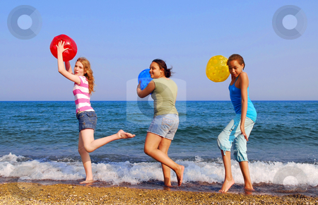Girls on beach stock photo, Three girls with colorful beach balls walking on sea shore by Elena Elisseeva