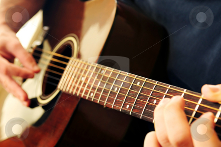 Man playing a guitar stock photo, Hands of a person playing an acoustic guitar by Elena Elisseeva