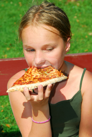 Girl pizza stock photo, Young girl eating a slice of cheese pizza outside by Elena Elisseeva