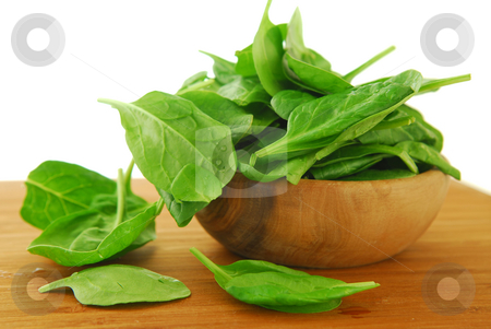 Spinach stock photo, Fresh spinach iin a wooden bowl on a cutting board by Elena Elisseeva
