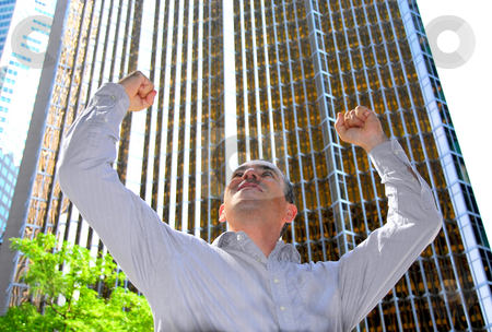 Businessman truimph stock photo, Triumphant businessman in the city raising arms in victory by Elena Elisseeva