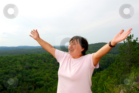 Carefree woman stock photo, Mature woman on hilltop raising her arms by Elena Elisseeva