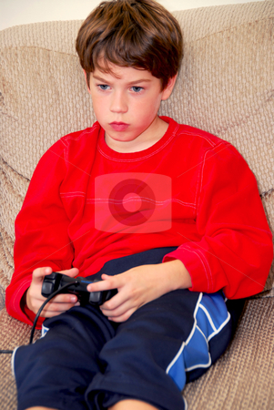 Boy video game stock photo, Young boy playing a video game sitting on a couch by Elena Elisseeva