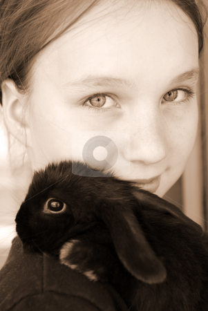 Girl and bunny stock photo, Portrait of a young girl holding a black baby rabbit in sepia by Elena Elisseeva