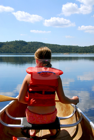 Child in canoe stock photo, Child in canoe paddling on a scenic lake by Elena Elisseeva