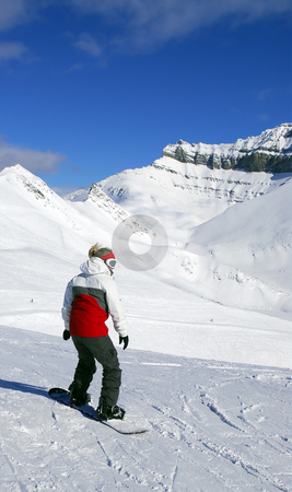 Mountains snowboarding stock photo, Girl snowboarding on the backdrop of scenic view in Canadian Rocky mountains ski resort by Elena Elisseeva