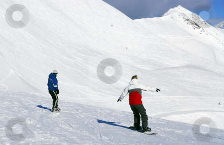 Mountains snowboarding stock photo, Couple snowboarding on the backdrop of scenic view in Canadian Rocky mountains ski resort by Elena Elisseeva