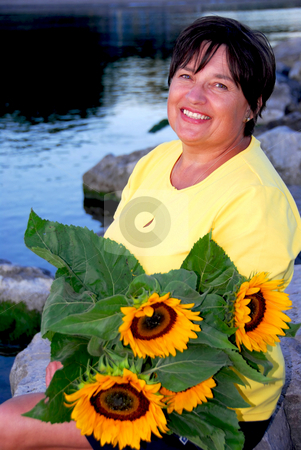 Woman sunflowers stock photo, Portrait of a mature woman with sunflowers by Elena Elisseeva