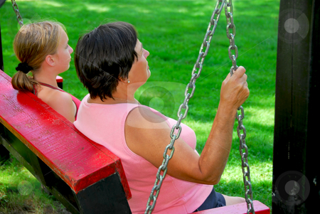 Family swings stock photo, Grandmother and granddaughter on swings side view by Elena Elisseeva