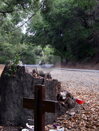 A turn in your path stock photo, A motorcycle, with rider, coming around a bend in the road. Foreground, a cross as part of a memorial for motorcycle accident victims at that site. by Rob Wright
