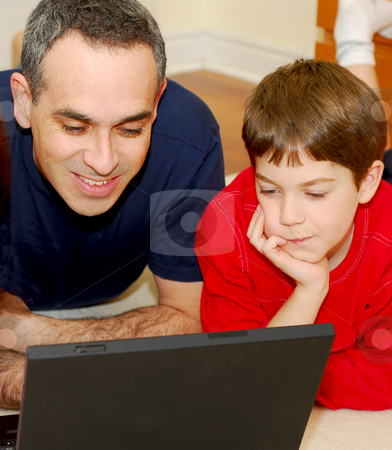 Father son computer stock photo, Father and son lying on the floor at home and looking into a portable computer by Elena Elisseeva