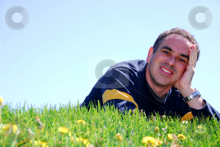 Smiling man on grass stock photo, Smiling man on resting on grass by Elena Elisseeva