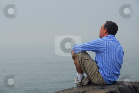 Man looking fog stock photo, Man sitting on a rocky shore, looking at the foggy ocean. Uncertain future concept by Elena Elisseeva