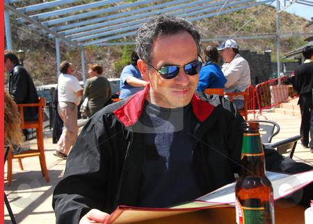 Man restaurant patio stock photo, Man sitting on a restaurant patio reading menu by Elena Elisseeva