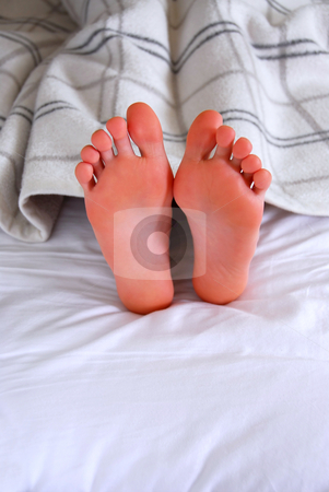 Child's feet stock photo, Child's feet sticking out of a blanket in a bed by Elena Elisseeva