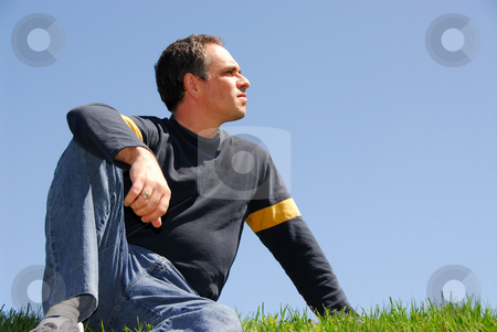 Man looking at sky stock photo, Man sitting on background of sky and grass, looking at sky by Elena Elisseeva