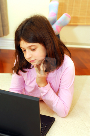 Girl computer stock photo, Young girl lying on the floor with portable computer by Elena Elisseeva