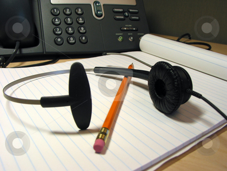 Customer support 4 stock photo, Headset, pencil and notepad on the office desk with IP phone in the background by Elena Elisseeva