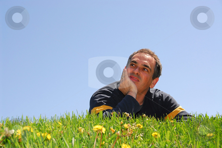Man on grass stock photo, Smiling man lying on grass on background of blue sky, looking up by Elena Elisseeva