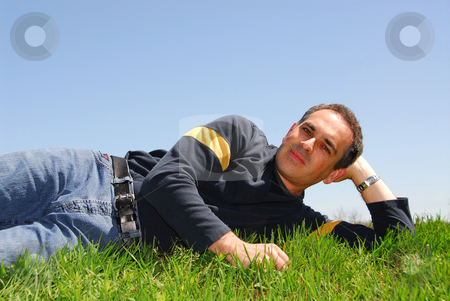 Man lying on grass stock photo, Smiling man lying on grass on background of blue sky by Elena Elisseeva