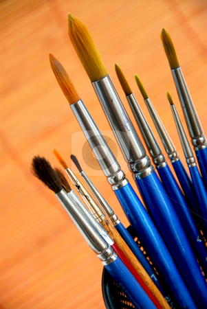 Paintbrushes holder stock photo, Paintbrushes in a metal mesh holder by Elena Elisseeva
