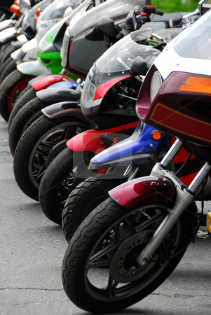 Row of motocycles stock photo, Row of motocycles parked on a street in front a motorcycle store by Elena Elisseeva