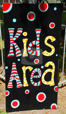 Kids Play Area sign stock photo, A photograph of a sign for a 'kids' area', situated outdoors in front of the fence around a play park by Philippa Willitts