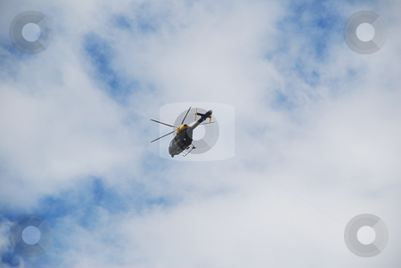 Police Helicopter in a Cloudy Blue Sky stock photo, A photograph of a helicopter with moving rotar blades, far away under a blue sky by Philippa Willitts