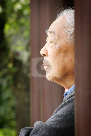 Garden Solace stock photo, An elderly Asian man rests in thought looking over still water at a Chinese garden. by Nathan Smith