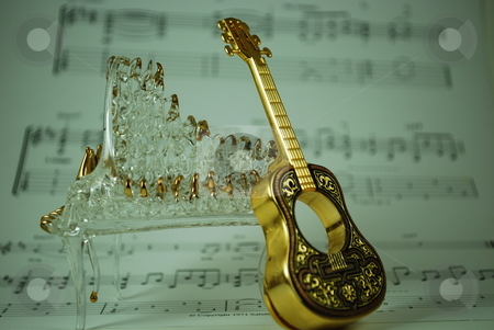 Guitar and piano stock photo, Guitar and glass piano against sheet music by Robert Cabrera