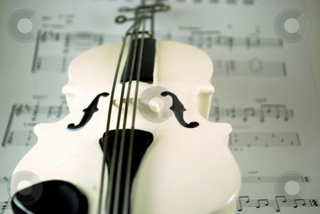 Bass with sheet music stock photo, Bass against sheet music by Robert Cabrera