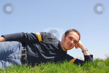 Man grass sky stock photo, Man lying outside on a grass on a background of cloudless blue sky by Elena Elisseeva