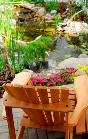Pond stock photo, Natural stone pond and wooden patio chair as landscaping design element by Elena Elisseeva