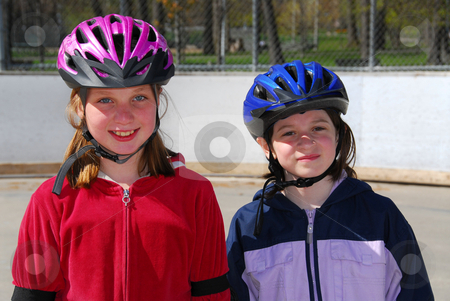 Two girls rollerblading stock photo, Two happy girls rollerblading in helmets by Elena Elisseeva