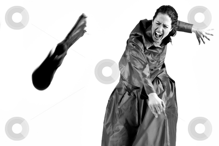 Hysterical woman with long curly hair  stock photo, Portrait of a woman with long curly hair throwing her boot away hysterically by Frenk and Danielle Kaufmann