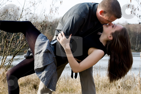 Young couple kissing stock photo, Young loving couple are hugging in the park by Frenk and Danielle Kaufmann