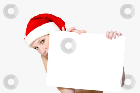 Copy space for christmas stock photo, Young woman dressed in santa's outfit hiding behind a blank sign by Frenk and Danielle Kaufmann