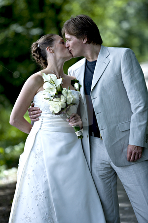 Wedding couple kissing stock photo, Wedding couple posing with a kiss by Frenk and Danielle Kaufmann