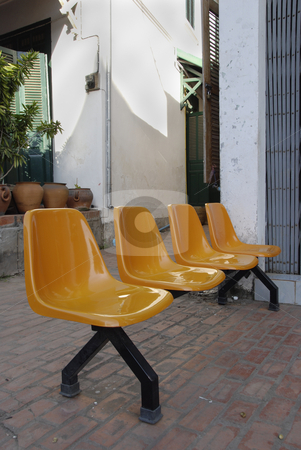 Orange Chairs stock photo, Orange chairs standing in the sun outside a shop by Claudia Van Dijk