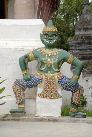 Buddhistic God stock photo, Buddhistic God standing next to a temple in Luang Prabang, Laos by Claudia Van Dijk