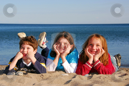 Three children on a beach stock photo, Three children lying on a beach laughing by Elena Elisseeva