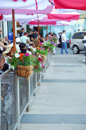 Sidewalk cafe stock photo, Sidewalk cafe behind a fence decorated with flowers full of people by Elena Elisseeva