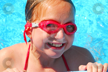 Girl portrait pool stock photo, Portrait of a smiling girl in red goggles resting at the pool edge by Elena Elisseeva