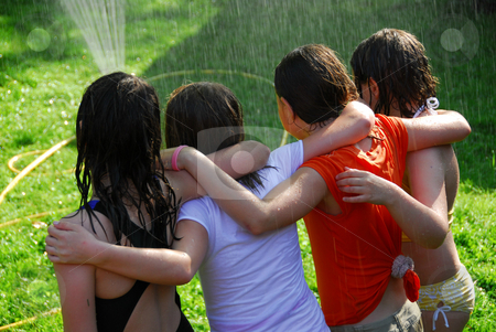 Group of girls and sprinkler stock photo, Group of preteen girls having fun outside running through sprinkler by Elena Elisseeva
