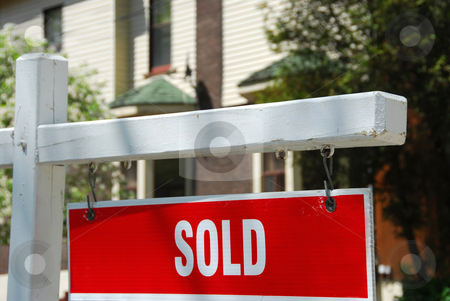 Sold house sign stock photo, Closeup on sold sign near residential house by Elena Elisseeva